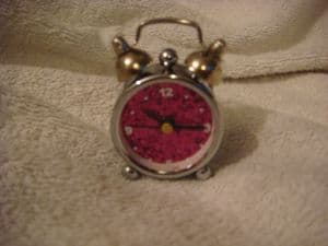 mini clock in shape of an alarm clock with pink face.
