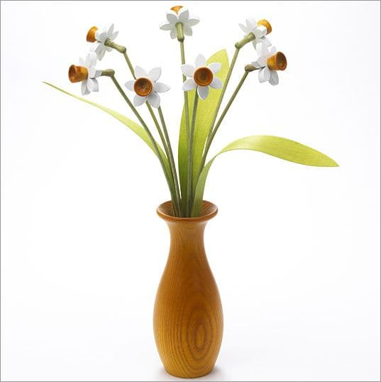 7 white Daffodils with 3 green leaves with yellow 'classic' vase